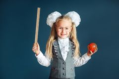 Funny little girl in school uniform wearing eyeglasses imitates a strict teacher against blue background. Looking at camera. Funny little girl wearing royalty free stock image