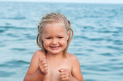 Funny little girl on sea background Stock Image