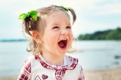 Funny little girl shouting at the sea Stock Photos