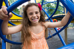 Funny little girl showing toothy smile. Cute little schoolgirl on the playground at summer day Royalty Free Stock Image