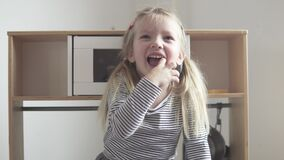 Funny little girl shows on her fingers that she is 4 years old