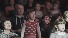 Funny little girl singing and repeat after performers on scene in concert hall stock video