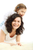 Funny little girl sits on mother which lying Royalty Free Stock Photo