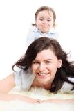 Funny little girl sits on mother which lying Stock Photography