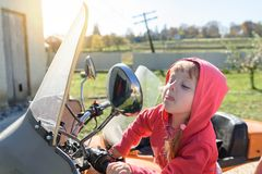 Funny little girl sits on a motorcycle, looks in the mirror and shows tongue, careless childhood Royalty Free Stock Image