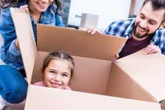 funny little girl sitting in cardboard box while happy parents looking stock image
