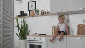 Funny little girl sitting in the kitchen and eagerly eating a loaf of white bread. stock video