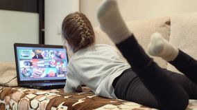 Funny little girl sitting on sofa using laptop and smiling stock footage