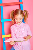 Funny little girl sitting on the stairs and reading book. Royalty Free Stock Image
