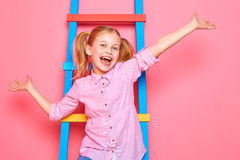 Funny little girl sitting on the stairs, waving hands and laughing Stock Image