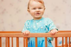 Funny little girl standing in the crib and smiling Stock Image