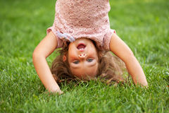 Funny little girl standing on her head Royalty Free Stock Photo
