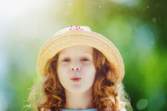 Funny little girl in a straw hat, shaped his lips for a kiss. Royalty Free Stock Image