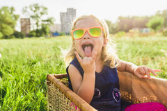 Funny little girl in sunglasses. Child girl in sunglasses looking up in yellow sunlight on summer day background Stock Photos