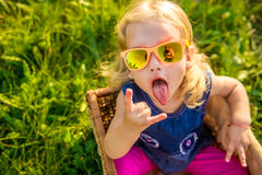 Funny little girl in sunglasses. Child girl in sunglasses looking up in yellow sunlight on summer day background Stock Photography