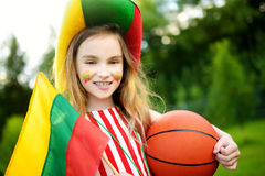 Funny little girl supporting and cheering her national basketball team during basketball championship. Stock Image