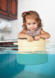 Funny little girl swim in pan in the flooded kitchen, rowdy crea Royalty Free Stock Photo