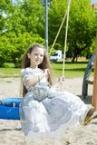 Funny little girl on the swing Stock Photo