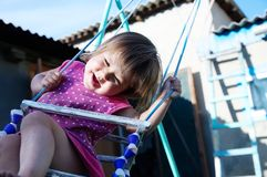 Funny little girl swing outdoor at summer, child playing. Activity royalty free stock photos