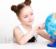 Funny little girl at the table of a first-grader. Stock Photo