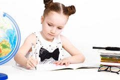 Funny little girl at the table of a first-grader. Stock Photography