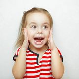 Funny little girl taken aback by great surprise. With wide open eyes and mouth holds her hands on cheeks and looks eways emotional portrait photo with wall stock photo