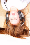Funny little girl upside down with headphones Royalty Free Stock Photography