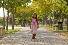 Funny little girl walking in the park Stock Photo