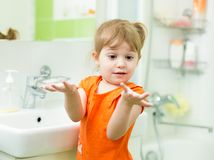 Funny little girl washing hands in bathroom Royalty Free Stock Images