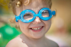 Funny little girl in water glasses Royalty Free Stock Image