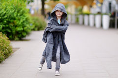 Funny little girl wearing her fathers' coat Royalty Free Stock Images