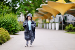 Funny little girl wearing her fathers' coat Royalty Free Stock Photography