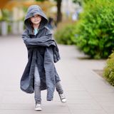Funny little girl wearing her fathers' coat Stock Photography