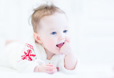 Funny little girl wearing a red and white snowflake sweater. Funny adorable little girl sucking on her finger and wearing a red and white snowflake sweater Stock Image