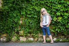 Funny little girl wearing sunglasses posing by bindweed wall on warm and sunny summer day Stock Photos