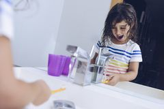 Funny little girl wetting the toothbrush. After taking a shower she prepares to brush her teeth in front of the mirror of the bathroom, kids hygiene concept royalty free stock image