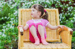 Funny little girl in wicker chair Royalty Free Stock Images
