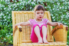 Funny little girl in wicker chair Royalty Free Stock Photo