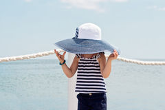 Funny little girl (3 years) in big hat on the beach. Selective focus Royalty Free Stock Images