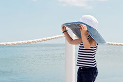 Funny little girl (3 years) in big hat on the beach. Selective focus Royalty Free Stock Photo