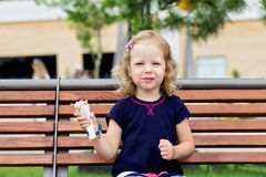 Funny little girl (3 years) eat ice cream. Royalty Free Stock Image