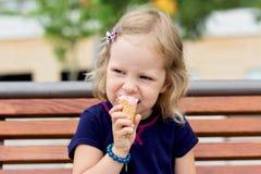 Funny little girl (3 years) eat ice cream. stock image