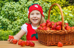 A funny little girl 4 years old with a basket of strawberries Stock Images