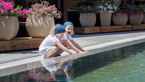 Funny little girls (sisters) are playing near the pool. Royalty Free Stock Photography