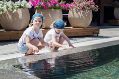 Funny little girls (sisters) are playing near the pool. Stock Photography