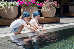 Funny little girls (sisters) are playing near the pool. Stock Photos
