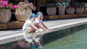 Funny little girls (sisters) are playing near the pool. Stock Images