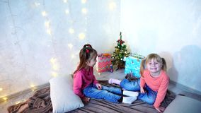 Active young children of girls laugh and fool around, sitting on floor and on rug, against background of wall with. Funny little girls smile and pose in camera stock video