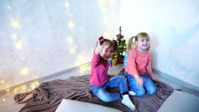 Active young children of girls laugh and fool around, sitting on floor and on rug, against background of wall with. Funny little girls smile and pose in camera stock footage