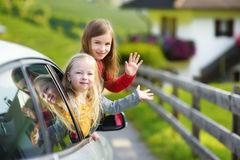 Funny little girls sticking their heads out the car window looking forward for a roadtrip or travel. Traveling by car with kids Stock Image